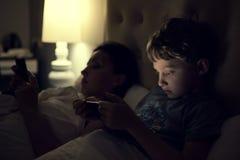 Moeder met het gebruiken van moderne apparaten vóór slaap Stock Fotografie