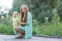Moeder met het kleine dochter rusten in park Stock Afbeeldingen