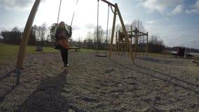 Moeder met het meisjesschommeling van de babydochter in park 4K stock footage