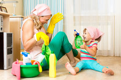 Moeder met jong geitje schoonmakende ruimte en het hebben van pret Stock Fotografie