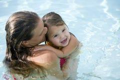 Moeder met jong meisje in zwembad stock afbeeldingen