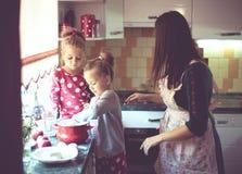 Moeder met jonge geitjes bij de keuken Stock Foto's