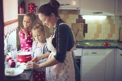 Moeder met jonge geitjes bij de keuken Royalty-vrije Stock Afbeelding