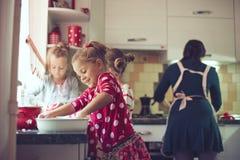 Moeder met jonge geitjes bij de keuken Stock Afbeelding