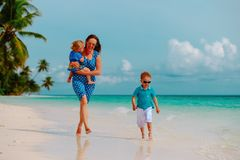 Moeder met jonge geitjesspel op tropisch strand in werking dat wordt gesteld dat royalty-vrije stock afbeelding
