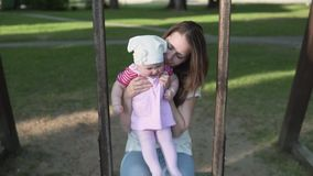 Moeder met kind buiten het slingeren op houten schommeling in groen park stock footage