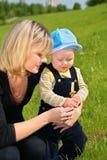 Moeder met kind en paardebloem op weide stock fotografie