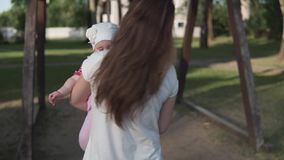 Moeder met kind het gaan op een houten schommeling bij zonsondergang berijden stock videobeelden