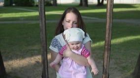 Moeder met kind het slingeren op houten schommeling, camera het volgende stock videobeelden