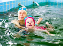 Moeder met kind het zwemmen in een pool royalty-vrije stock afbeelding