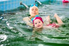 Moeder met kind het zwemmen in een pool stock fotografie