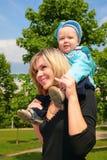 Moeder met kind op schouders openlucht