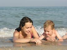 Moeder met kind op strand Stock Foto