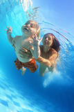 Moeder met kind zwemmen onderwater in de pool Stock Afbeeldingen
