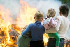 Moeder met kinderen bij het branden van huisachtergrond Stock Foto's