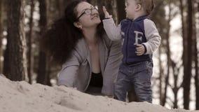 Moeder met kinderen die met zand spelen stock footage