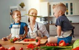 Moeder met kinderen die plantaardige salade voorbereiden royalty-vrije stock afbeeldingen