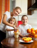 Moeder met kinderen gedrukt jus d'orange Royalty-vrije Stock Afbeelding