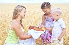 Moeder met kinderen op een gebied van tarwe stock afbeelding