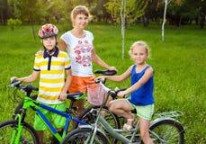 Moeder met kinderen op fietsen stock fotografie