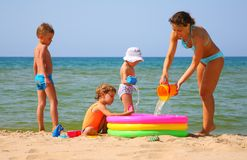 Moeder met kinderen op overzees en pool Stock Afbeelding