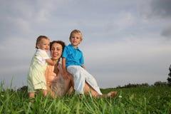 Moeder met kinderen op weide Royalty-vrije Stock Foto's