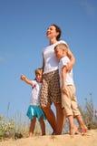 Moeder met kinderen openlucht op zand Stock Afbeelding