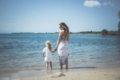 Moeder met kindmeisje door het overzees Zonsondergangportret openlucht De zomer Vrouw met meisje Royalty-vrije Stock Foto