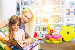 Moeder met meisje gelezen boek samen royalty-vrije stock foto's