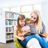 Moeder met meisje gelezen boek samen in bibliotheek stock afbeeldingen