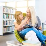 Moeder met meisje gelezen boek samen in bibliotheek stock foto's