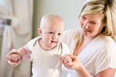 Moeder met oude baby leren het van zeven maanden te lopen Royalty-vrije Stock Afbeeldingen