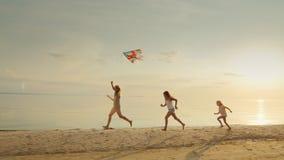 Moeder met twee dochters die op het strand met een vlieger spelen De samen in werking gestelde pret stock videobeelden