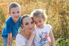 Moeder met twee kinderen in gouden tarwe Stock Fotografie