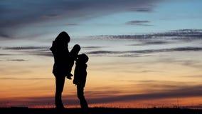 Moeder met twee kinderensilhouetten, babyspel met grotere broer, zonsonderganghemel stock footage