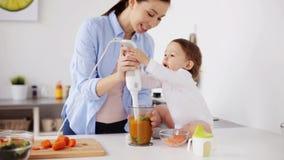 Moeder met voedsel van de mixer het kokende baby thuis stock footage