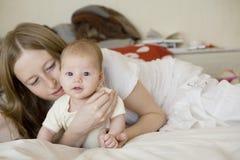 moeder met weinig baby die op bed ligt Stock Afbeelding