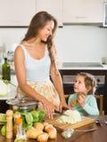 Moeder met weinig dochter die thuis koken Royalty-vrije Stock Afbeeldingen