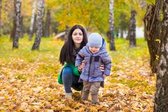 Moeder met weinig zoon in park op achtergrond van de herfstbladeren stock foto's