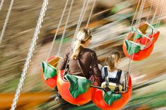 Moeder met zich dochter het bewegen snel op carrousel Gevangen motieonduidelijk beeld, geconcentreerd op organismen stock foto's