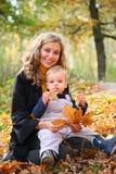 Moeder met zoon in bos in de herfst royalty-vrije stock afbeelding
