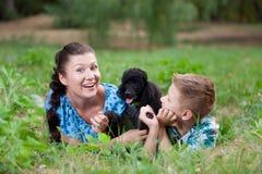 Moeder met zoon en een zwarte poedel Royalty-vrije Stock Afbeelding