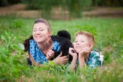 Moeder met zoon en een zwarte poedel Stock Foto's