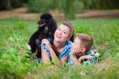 Moeder met zoon en een zwarte poedel Stock Foto