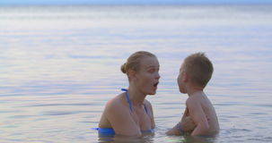 Moeder met zoon het baden in overzees en het hebben van pret stock footage