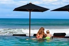 Moeder met zoon het koelen in strand zwembad Stock Fotografie