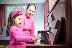 Moeder of Muzikale Leraar Teaching Little Girl hoe te om Piano te spelen Stock Foto's