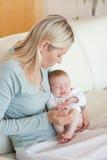 Moeder op de bank met haar baby op haar overlapping stock afbeelding