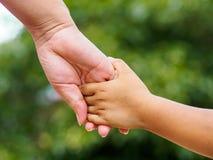 Moeder` s hand die een kleine meisjes` s hand op bokehachtergrond houden royalty-vrije stock afbeeldingen