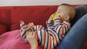Moeder` s handen die met baby zoons` s voeten spelen stock footage